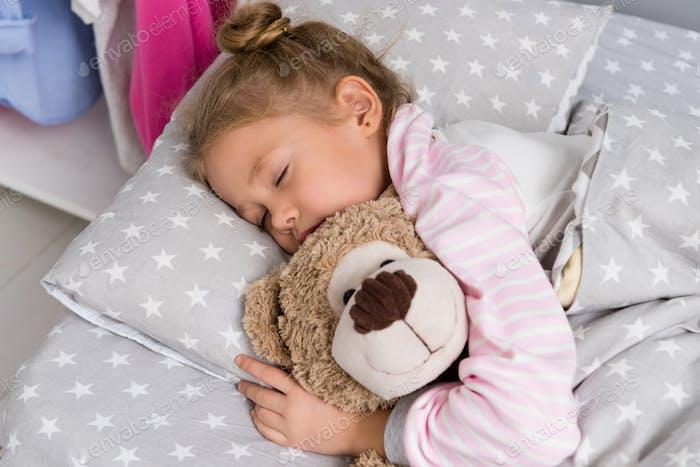entzückendes kleines Kind schläft mit Teddybär