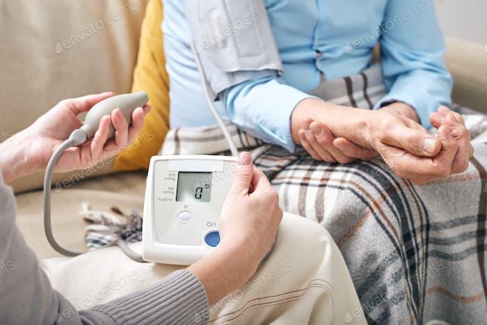 Checking blood pressure of senior