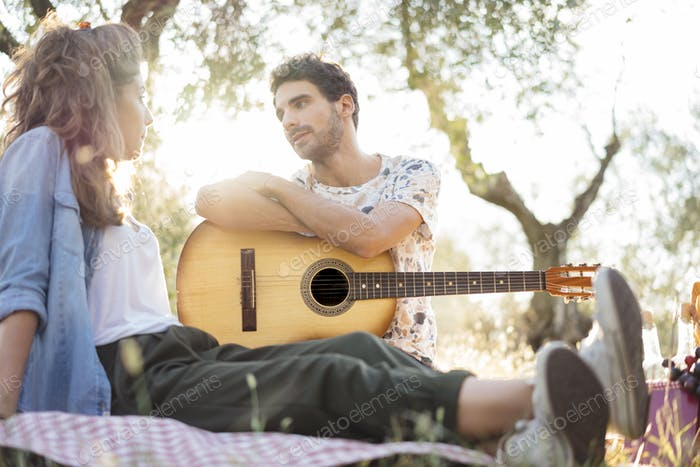 Young man playing guitar during a picnic to his girlfriend