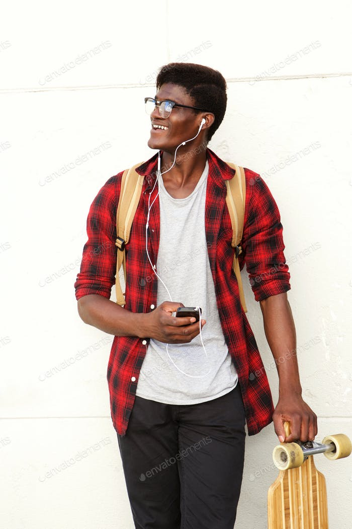 happy young black man standing with mobile phone and skateboard