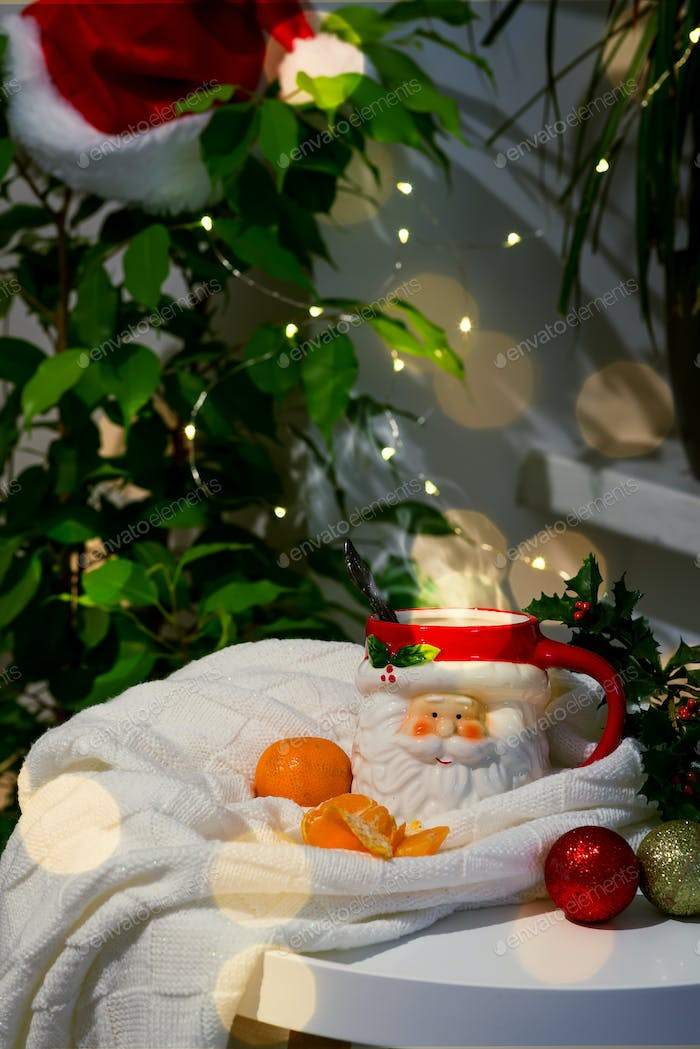 A cup in the form of Santa with hot tea and tangerines in a plaid with highlights on a background of