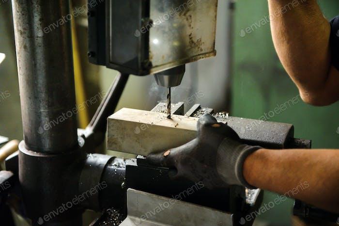 Worker drilling an aluminium block