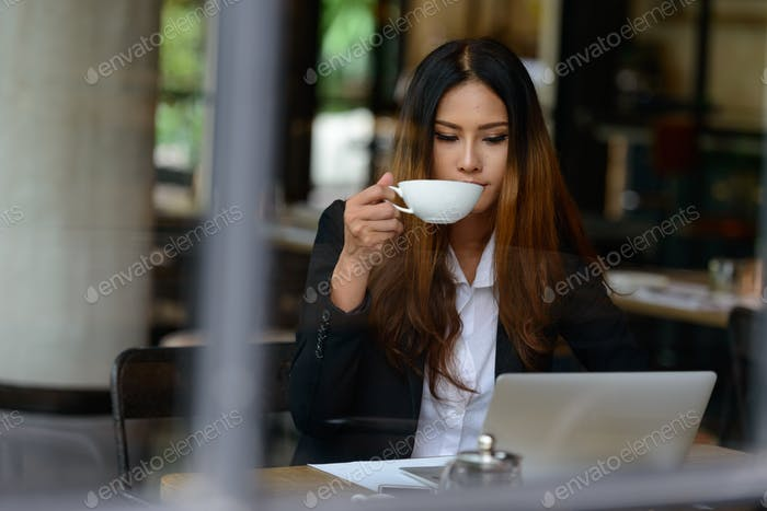 Young Asian businesswoman drinking coffee while working at cafe