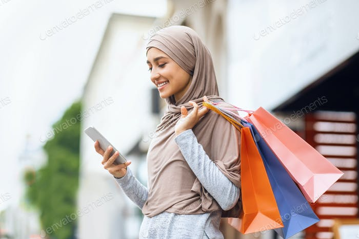 Happy arab woman with shopping bags using smartphone
