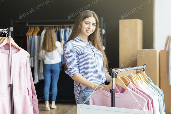 Smiling girl choosing new sweater at shop