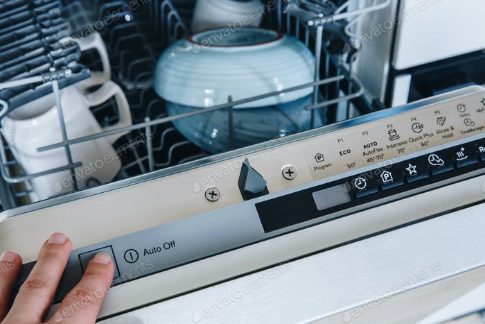Close-up of woman's finger pressing start button on dishwasher in the kitchen.