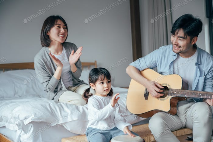 Happy family playing instruments in bedroom