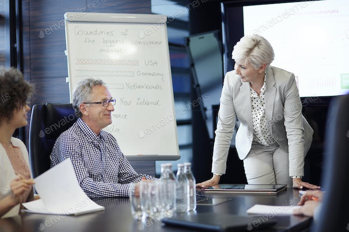 Mature coworkers talking at conference table