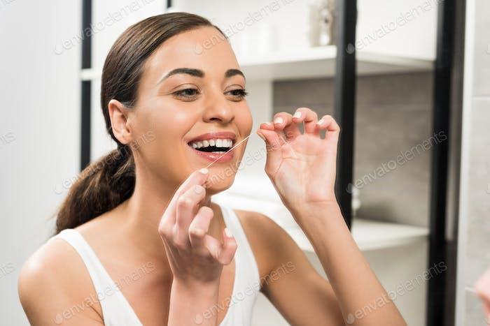 fröhliche brünette Frau mit Zahnseide im Badezimmer