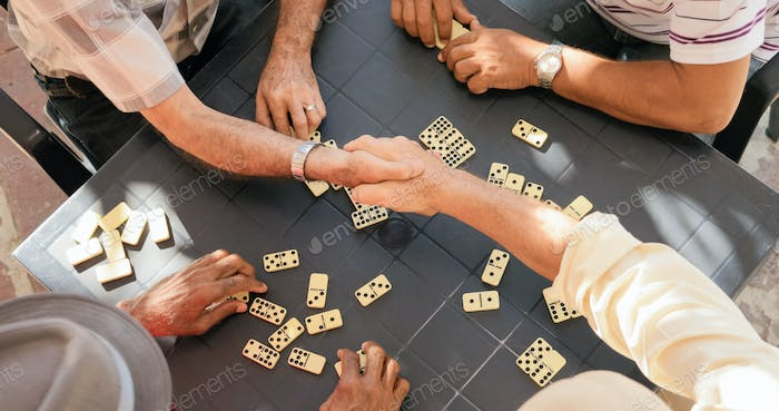 Senior Friends Shaking Hands Winning Game Of Domino