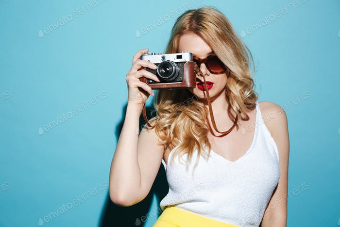 Young blonde woman in sunglasses taking picture on retro camera