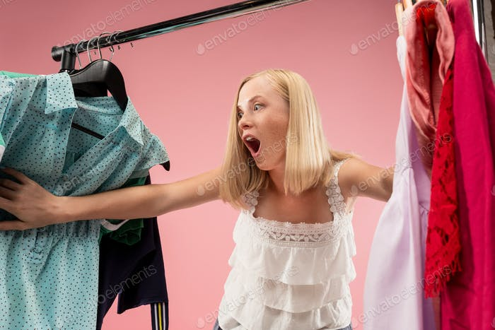 The young pretty girl looking at dresses and try on it while choosing at shop