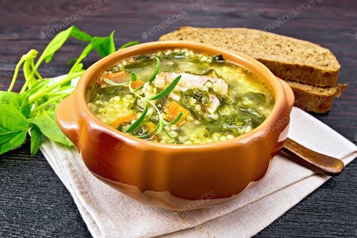 Suppe mit Couscous und Spinat in Tonschale auf Holztisch