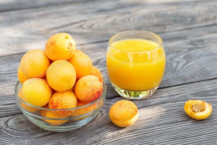 Gelbe Aprikosen in Glasschale und Saft auf Holztisch