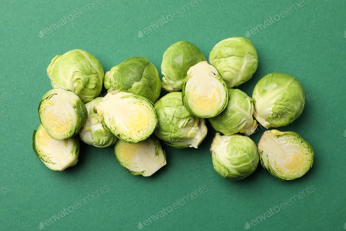 Heap of brussels sprout on green background, top view
