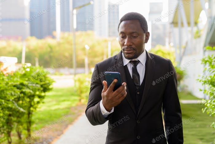 Handsome bearded African businessman in suit using phone at the park
