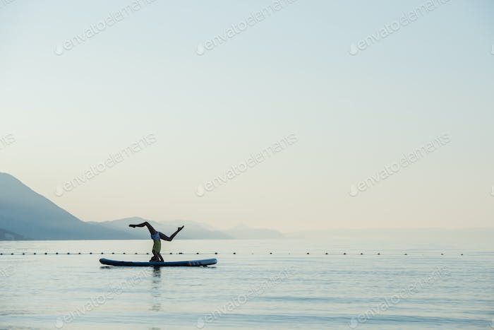 Woman making head stand on sup board