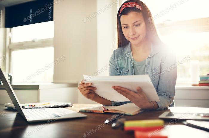 Young female entrepreneur doing paperwork at laptop