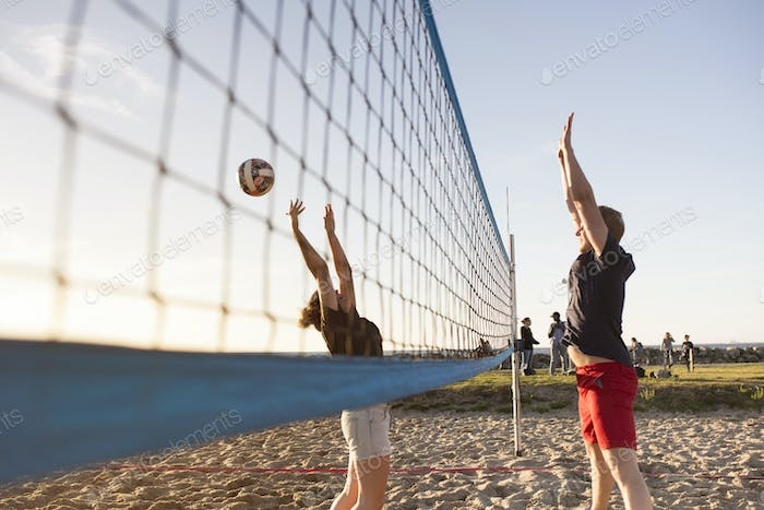 Friends playing volleyball on beach