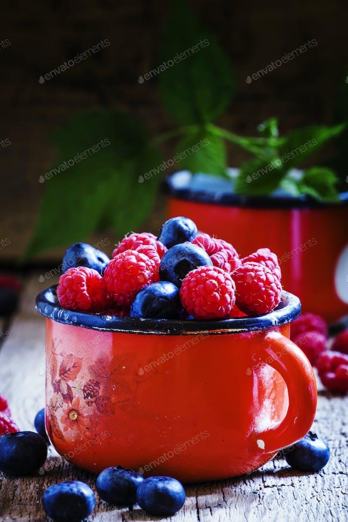 Fresh raspberries and blueberries in red enamel mug