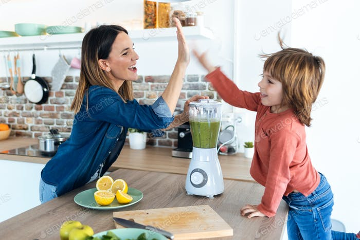 young mother and her son giving high five after preparing a detox smoothie together