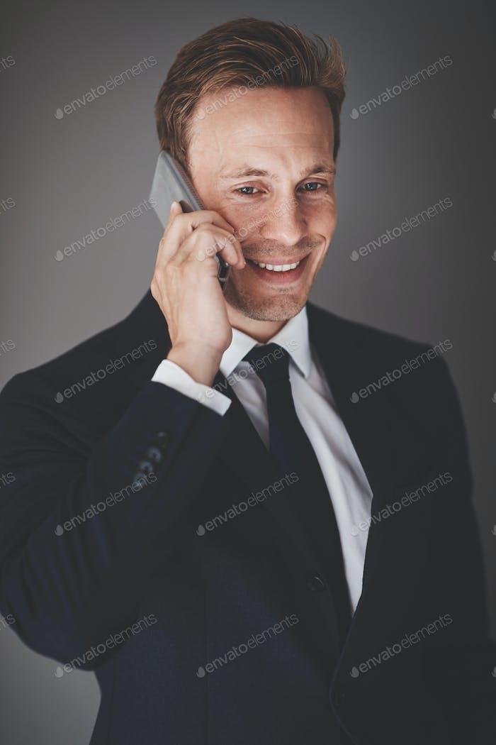 Lächelnd Geschäftsmann im Gespräch auf seinem Handy vor einem grauen Hintergrund