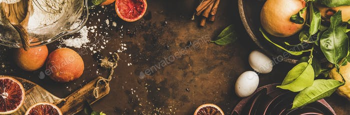 Blood orange cake ingredients over dark rusty background, wide composition