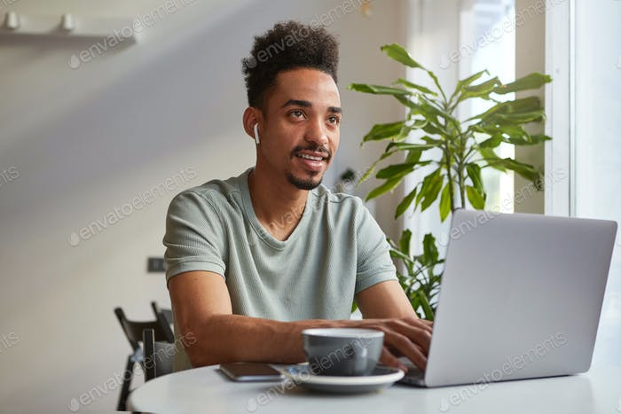 Portrait of young attractive African American thinking boy, sits at a table in a cafe