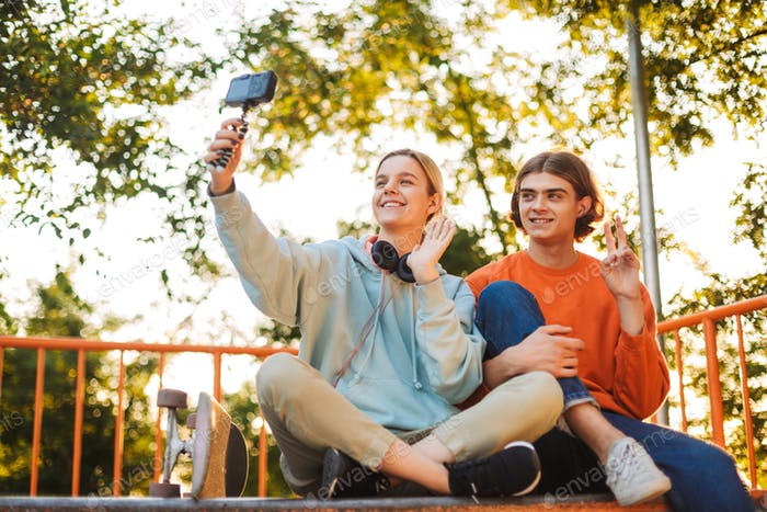 Young skater boy and girl with headphones happily waving on came