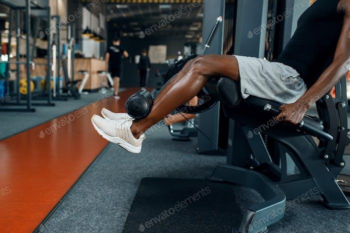 Atleta muscular en ropa deportiva en la máquina de ejercicios