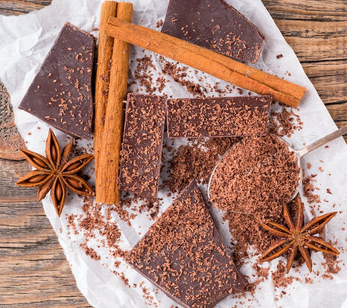broken pieces of chocolate, anise star, cinnamon sticks, crumb on parchment paper, top view