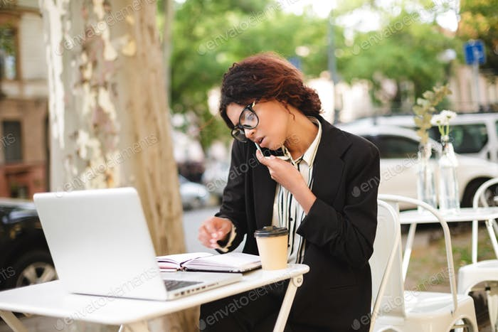 African American girl in glasses sitting at the table of cafe and talking on her cellphone working