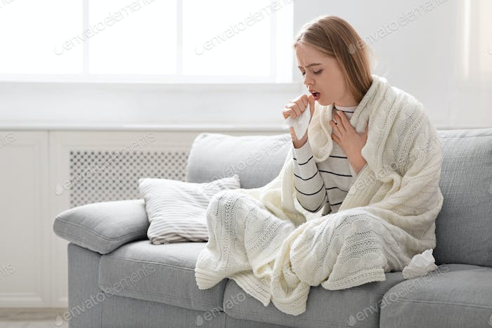 Sick young woman coughing at home, empty space