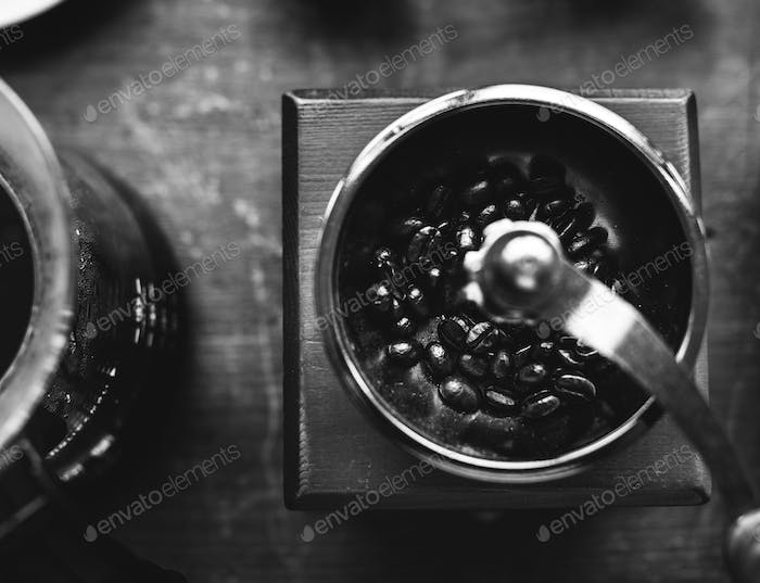 Closeup of coffee grinder on wooden table grayscale