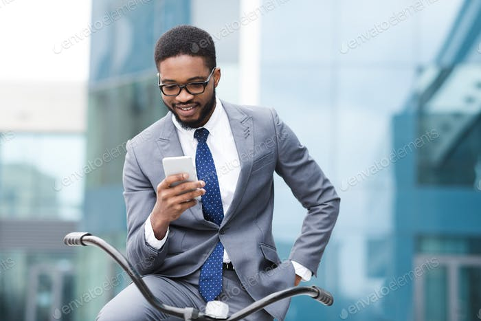 Handsome businessman texting on phone sitting on bike