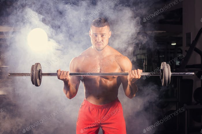 Power athletic man with barbell confidently looking forward