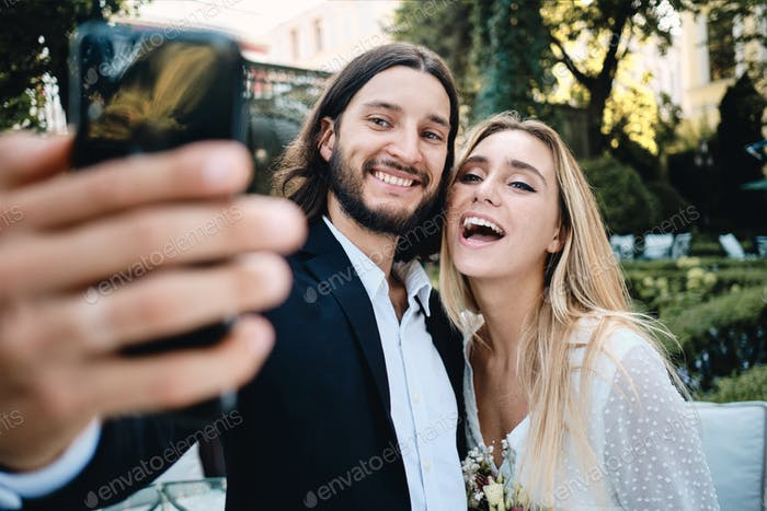 Young attractive cheerful groom and bride happily taking selfie together in garden of restaurant