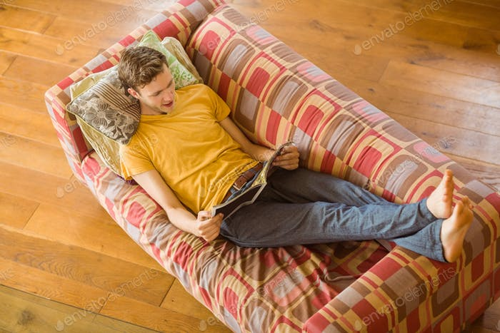Young man reading magazine on his couch at home in the living room