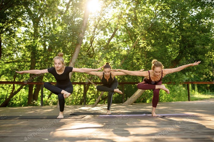 Three women doing balance exercise, group yoga