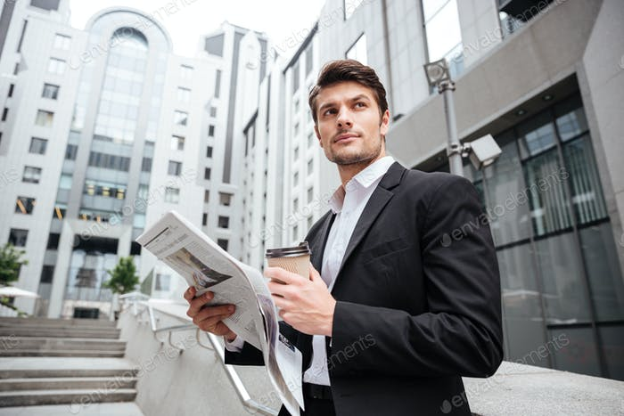 Businessman reading newspaper and drinking coffee in the city