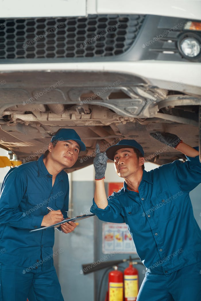 Mechanics inspecting car bottom