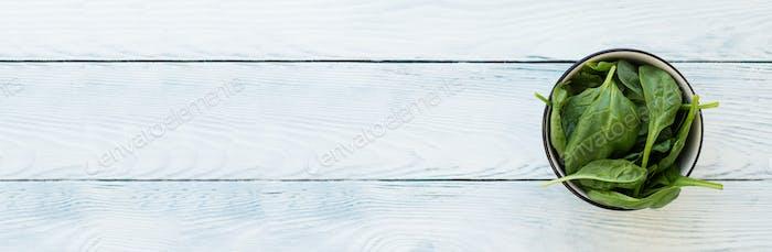 Spinatblätter auf weißem Holztisch. WebBanner