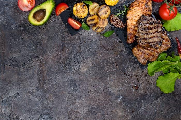 Frische drei Arten von gegrilltem Steak auf Schieferplatte mit Kräutern, Tomaten, Avocado und gegrillten Kartoffeln