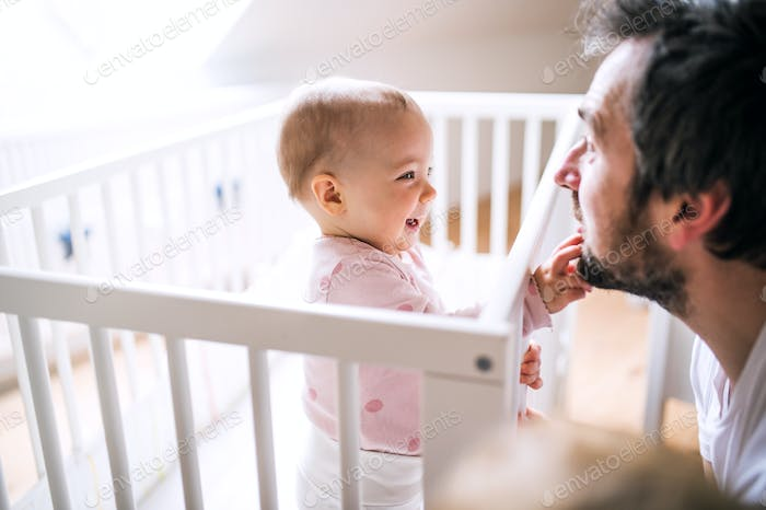 A small toddler girl standing in cot with her father at home.