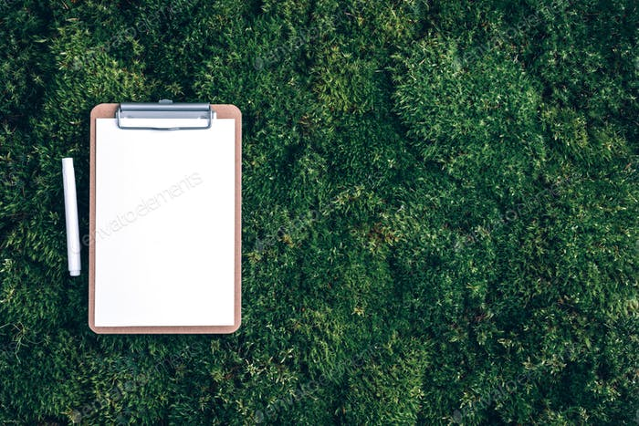 Notepad, pencil on green grass, moss background. Copy space. Top view. Office mock up, remote job