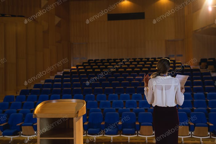 Businesswoman practicing and learning script while standing in the auditorium
