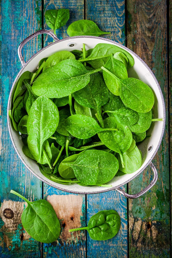 raw fresh spinach with drops in a colander