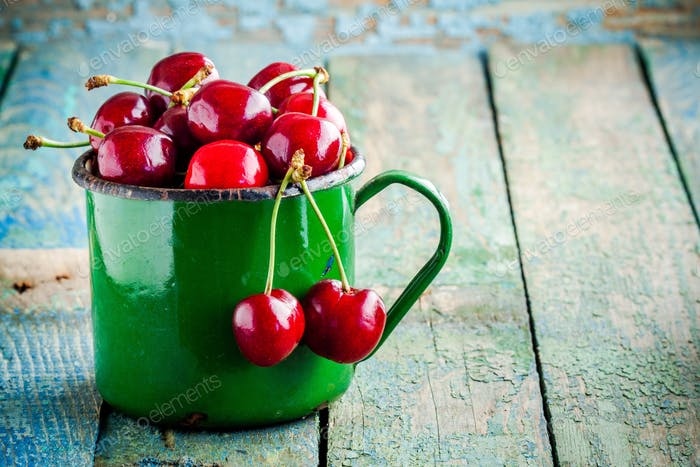 ripe juicy cherries in the old mug