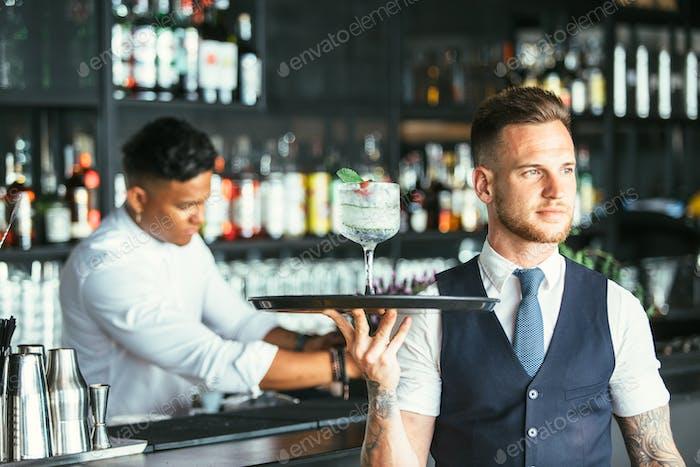 Elegant waiter serving a cocktail