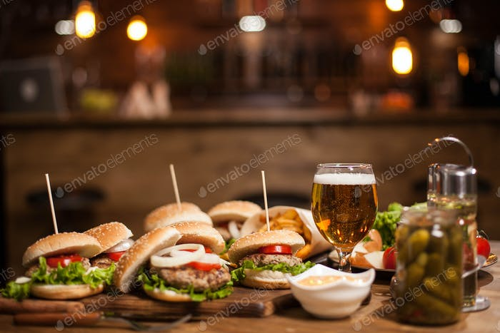 Tasty burgers with green salad on wooden table